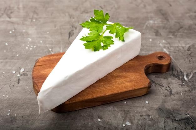 Queijo de pasta mole com mofo branco sobre uma tábua de madeira. decorado com salsa verde