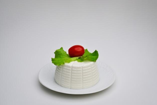 Queijo de ricota com folhas de manjericão e tomate cereja em fundo branco ricota com valeriana em prato branco ricota com salada em prato branco