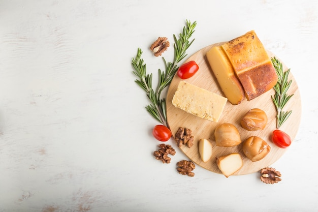 Queijo defumado e vários tipos de queijo com alecrim e tomate em uma placa de madeira sobre uma superfície de madeira branca