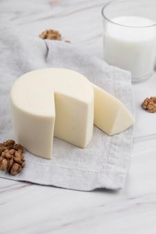 Queijo delicioso close-up com nozes e copo de leite