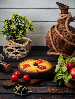 Queijo derretido coberto com fatias de tomate e azeitona em panela de cerâmica
