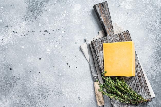 Queijo duro com faca na tábua de madeira. parmesão. plano de fundo cinza. vista do topo. copie o espaço.