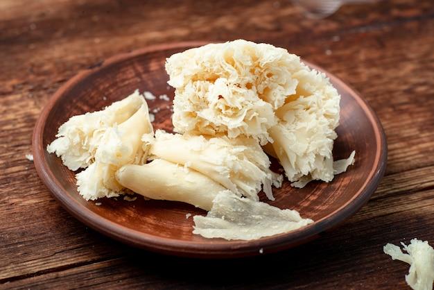 Queijo duro fatiado chips em um prato de barro em um fundo de madeira.