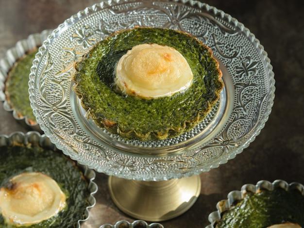 Queijo e espinafre de tartlet em uma tabela de madeira. comida saudável.