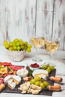 Queijo e salame em uma placa de ardósia e vinho de uva
