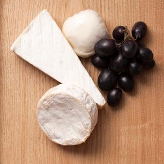 Queijo e uva na mesa de madeira