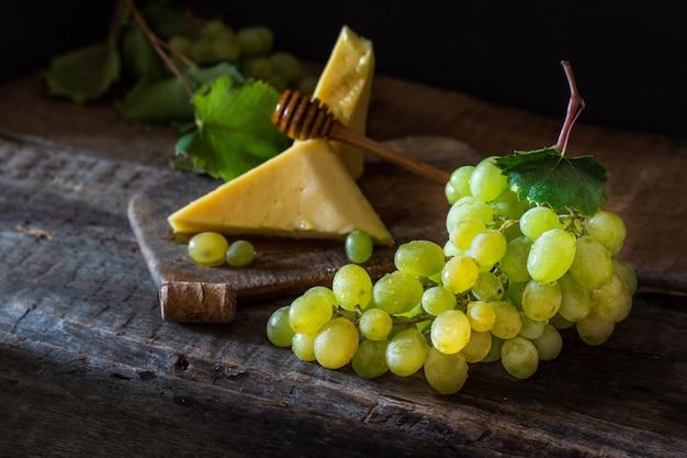 Queijo e uvas em uma madeira com nozes, mel. queijo francês. conceito de pequeno-almoço. ainda vida