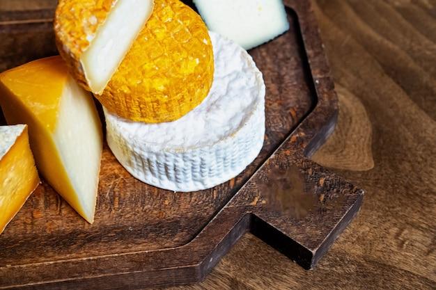 Queijo em uma placa de corte em uma mesa de madeira. fábrica de queijos e loja de queijos. produtos lácteos naturais da fazenda. publicidade e menus.