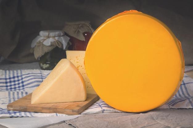 Queijo em uma placa de madeira, uma cabeça grande de queijo.