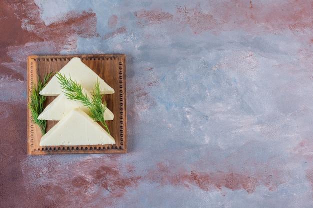 Queijo fatiado e endro em uma placa, no fundo de mármore.