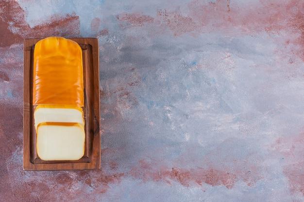 Queijo fatiado retangular em uma placa na superfície de mármore