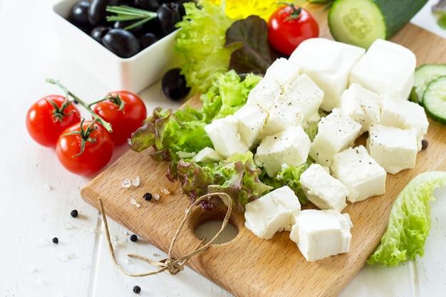 Queijo feta e azeitonas pretas cozinhando salada qreek com legumes frescos em uma mesa de madeira branca