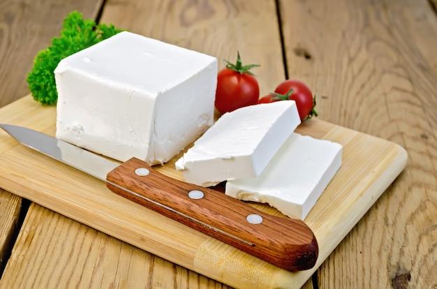 Queijo feta, faca, salsa e tomate em um fundo de tábuas de madeira