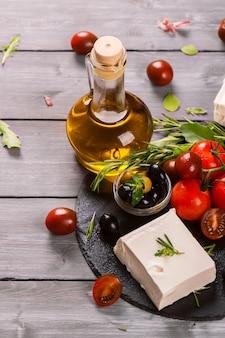 Queijo feta grego com ervas frescas, azeitonas pretas e verdes, tomate cereja, foco seletivo
