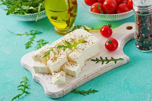 Queijo feta, tomate cereja e rúcula em cima da mesa. ingredientes para salada.