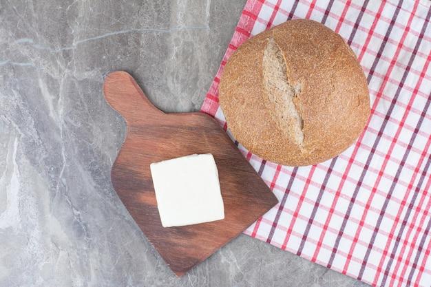 Queijo fresco branco com pão na toalha de mesa. foto de alta qualidade