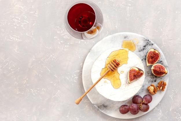 Queijo fresco brie com mel, nozes, figos e uvas.
