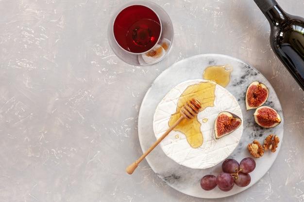 Queijo fresco brie com mel, nozes, figos, uvas e copo de vinho tinto.