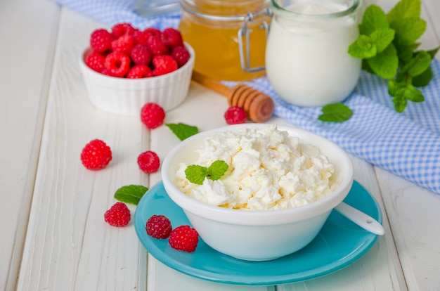Queijo fresco caseiro em uma tigela com frutas de framboesa, creme de leite e mel