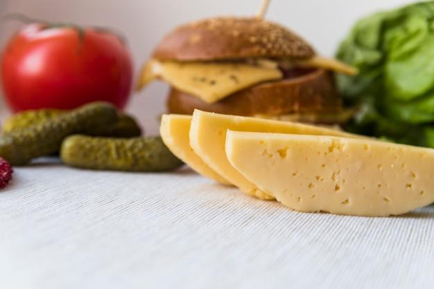 Queijo fresco perto de tomate, pepino e sanduíche na mesa