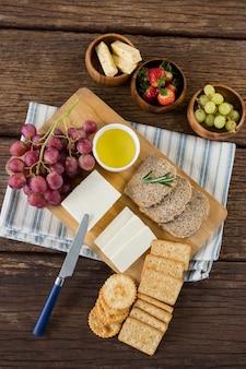 Queijo gouda, fatias de pão integral, biscoitos e frutas com suco de limão