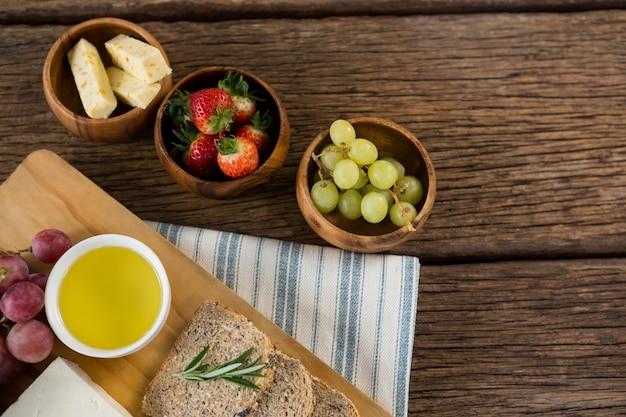 Queijo gouda, fatias de pão integral, suco de limão e frutas