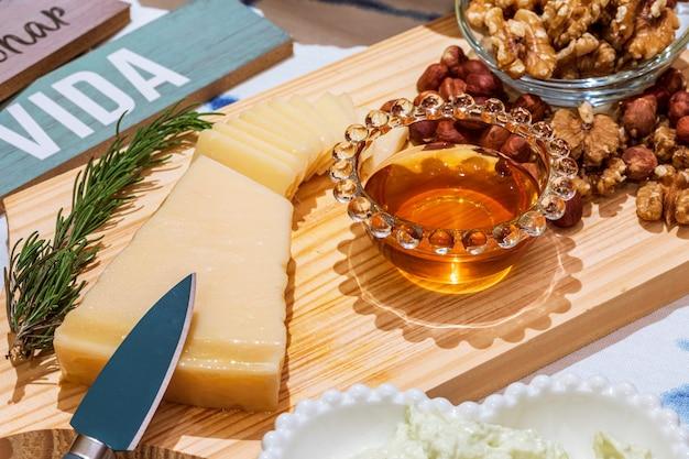 Queijo grana padano com mel e petiscos na mesa para degustação e cenário de férias.