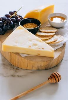 Queijo gruyere, uvas, nozes, mel e bolacha na placa de madeira em mármore