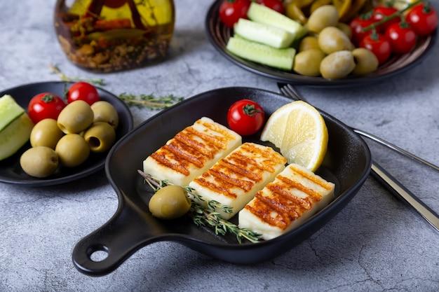Queijo haloumi grelhado em uma panela preta com azeitonas, tomates, pepinos e calabresa. fechar-se.