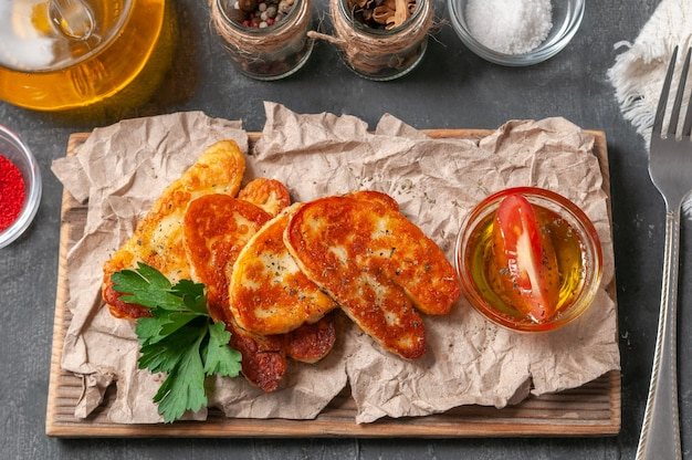 Queijo halumi fatiado com especiarias. em uma placa de madeira. decorado com especiarias e salsa. ao lado do queijo estão as taças com azeite, páprica, sal e especiarias. vista de cima. fundo cinza