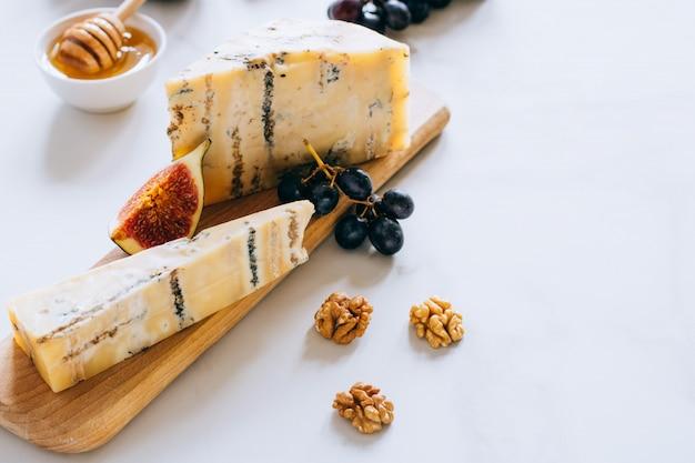 Queijo inglês velho de stilton. queijo azul, figos e uvas em uma tábua de cozinha em mármore