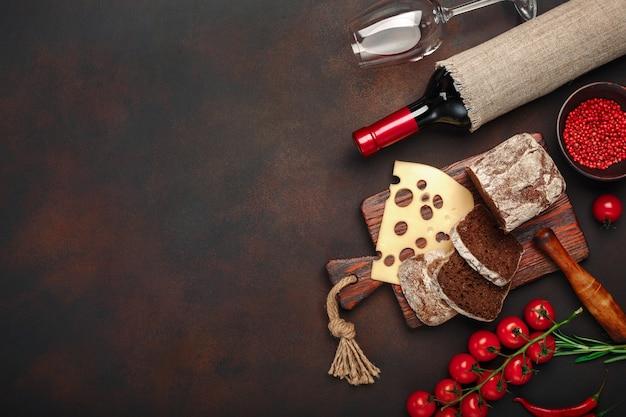 Queijo maasdam fatiado em uma tábua com tomate cereja, pão preto, alho e alecrim, garrafa de vinho