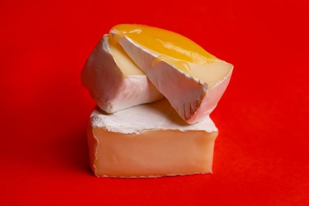 Queijo macio com mofo branco e mel em um fundo vermelho.