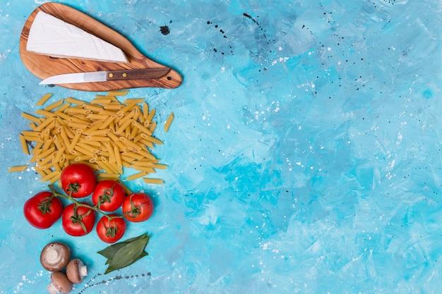 Queijo; massa de penne; tomates vermelhos; cogumelo e folhas de louro na superfície azul