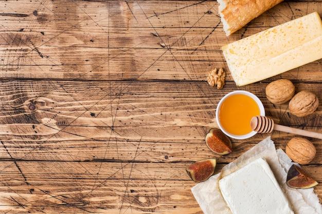 Queijo, mel do baguette e petiscos nuts no tampo da mesa de madeira rústico com espaço da cópia.