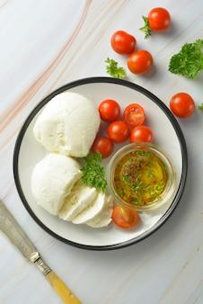 Queijo mussarela e tomate cereja com especiarias. queijo mussarela caseiro.