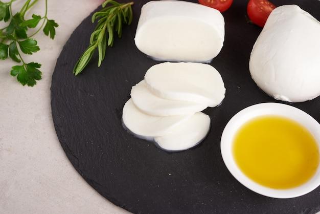 Queijo mussarela fresco, queijos italianos suaves, tomate e manjericão, azeite de azeitonas e alecrim na tábua de servir de madeira sobre uma superfície de madeira clara comida saudável. vista do topo. postura plana.