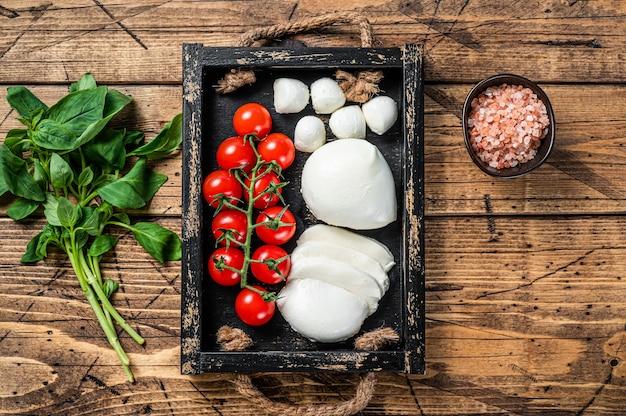 Queijo mussarela, manjericão e tomate cereja em bandeja de madeira, salada caprese. fundo de madeira. vista do topo.