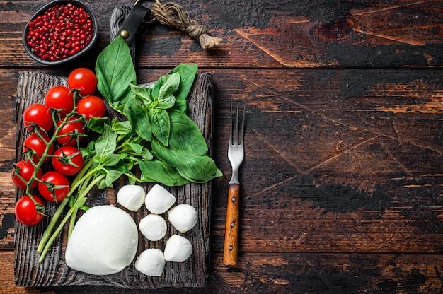 Queijo mussarela, manjericão e tomate cereja na placa de madeira, ingredientes para salada caprese. fundo de madeira escuro. vista do topo. copie o espaço.