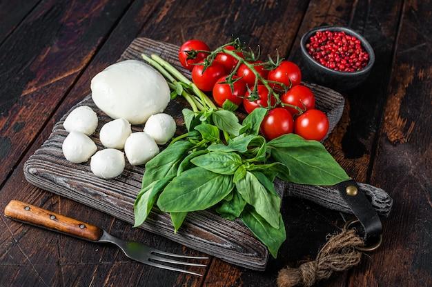 Queijo mussarela, manjericão e tomate cereja na placa de madeira, ingredientes para salada caprese. fundo de madeira escuro. vista do topo.