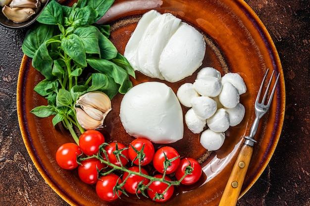 Queijo mussarela, manjericão e tomate cereja pronto para cozinhar salada caprese. fundo escuro. vista do topo.