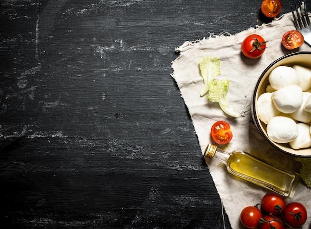Queijo mussarela, tomate, azeite e ervas em um tecido velho em um fundo preto de madeira