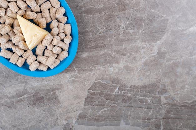 Queijo nas migalhas de pão na tigela ao lado da espiga, na superfície do mármore