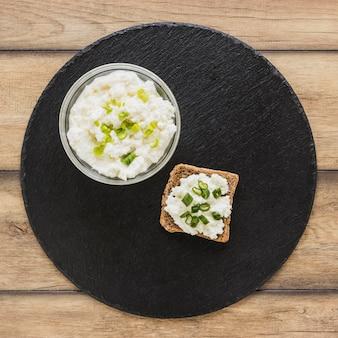Queijo no pão integral sobre a placa de servir de ardósia preta na mesa