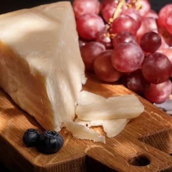 Queijo parmigiano na tábua de madeira com bagas de uva