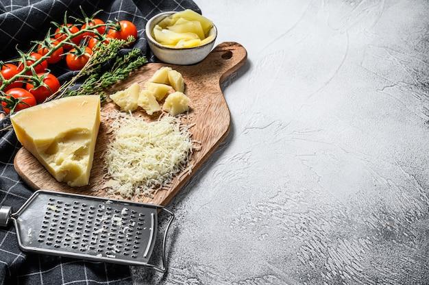 Queijo parmigiano reggiano ralado e ralador de metal na tábua de madeira.