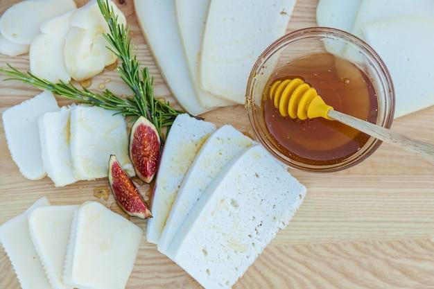 Queijo picado de diferentes variedades regado com mel, figos e uma xícara com mel em um fundo de tábua de madeira