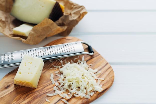 Queijo ralado com ralador de queijo e pedaço de queijo na mesa da cozinha