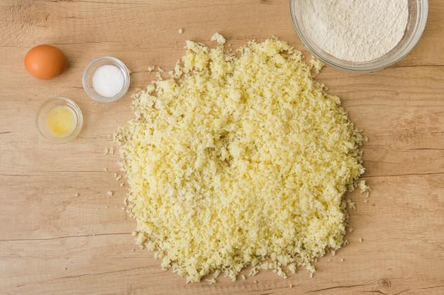 Queijo ralado; sal; ovo; farinha para preparar o nhoque italiano na mesa de madeira