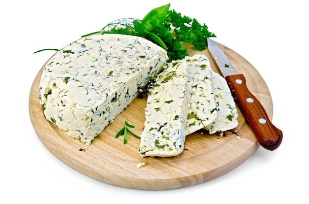 Queijo redondo caseiro com ervas e especiarias cortadas em fatias, faca em uma placa de madeira redonda isolada no fundo branco